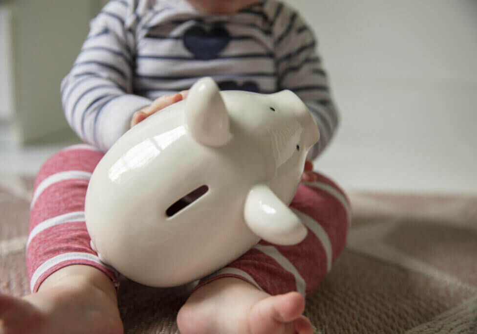 Cost of childcare concept. Young baby holds onto a white piggy bank